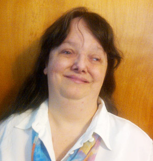 A white woman with long brown hair looks at the camera, smiling. She is wearing a white shirt, and posing in front of a light brown background.