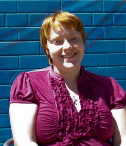 A headshot of Ms. Hyatt - a young woman with red hair wearing a pink shirt - smiling and facing the camera. The brick wall behind her is painted dark blue.