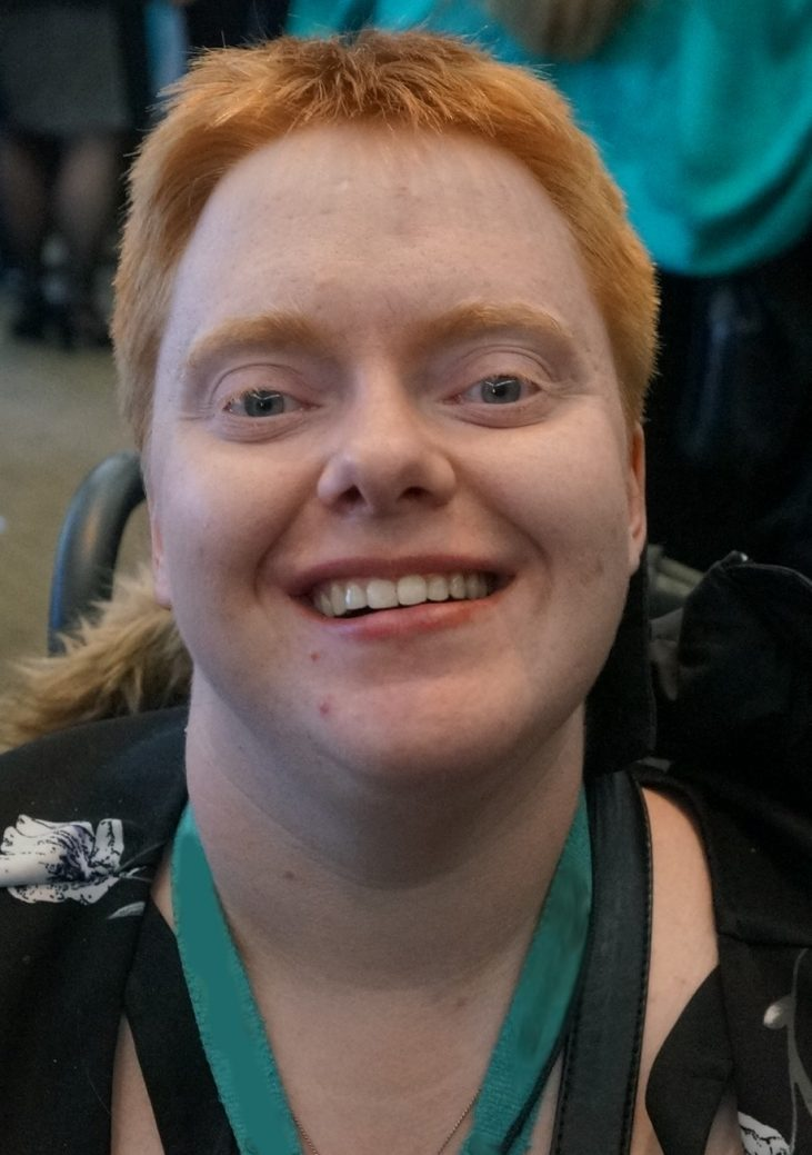 A headshot of a young white woman with short red hair smiles at the camera. She is wearing a black shirt with white flowers. Her purse strap is visible over her shoulders. A blue lanyard is around her neck. The fur trim of her jacket hood is visible; so is one handle of her wheelchair behind her, on the left.